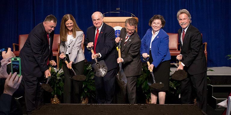 IU officials turn over shovels of dirt at a groundbreaking ceremony.