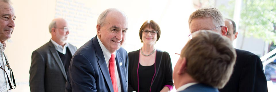 President McRobbie and others smile as they converse.
