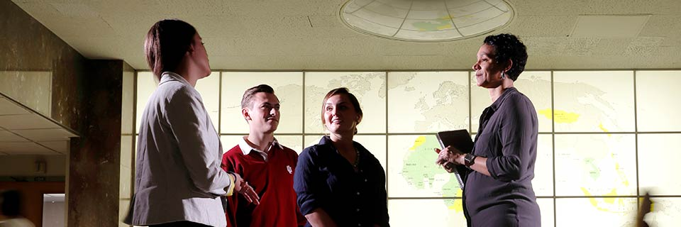 Three students talk with a professor in front of a lighted wall showing a world map.