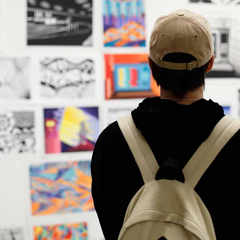 A student looks at drawings on a gallery wall.