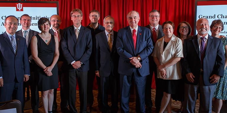 President McRobbie and others stand in front of a red backdrop at the announcement of the Grand Challenges initiative.
